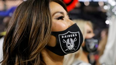 A member of the Las Vegas Raiderettes cheerleading squad wears a mask